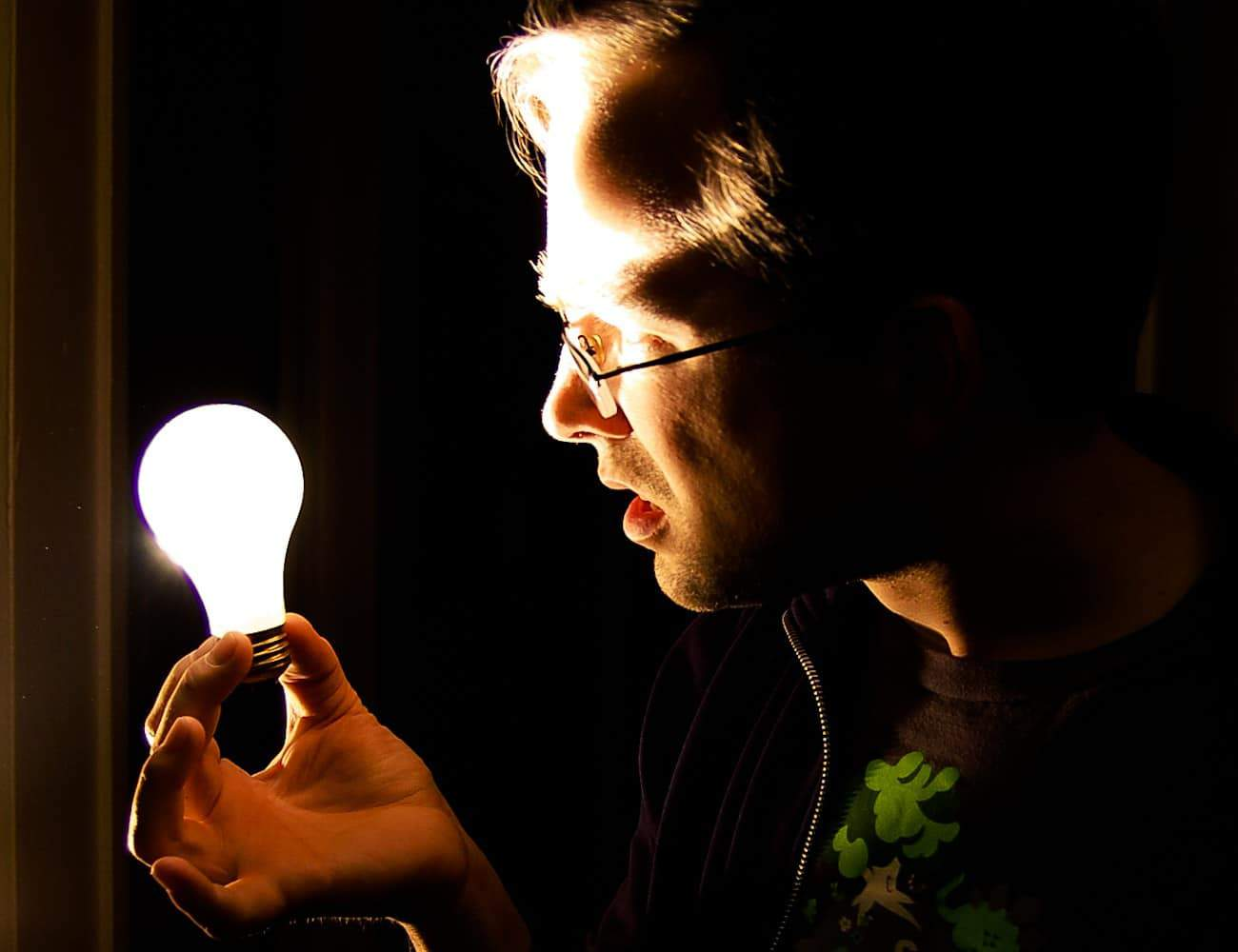 Man holding lightbuld. Procurement improvement requires enlightenment