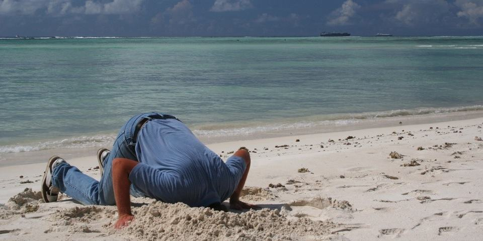 Disruption - Man with head in sand ignoring innovation
