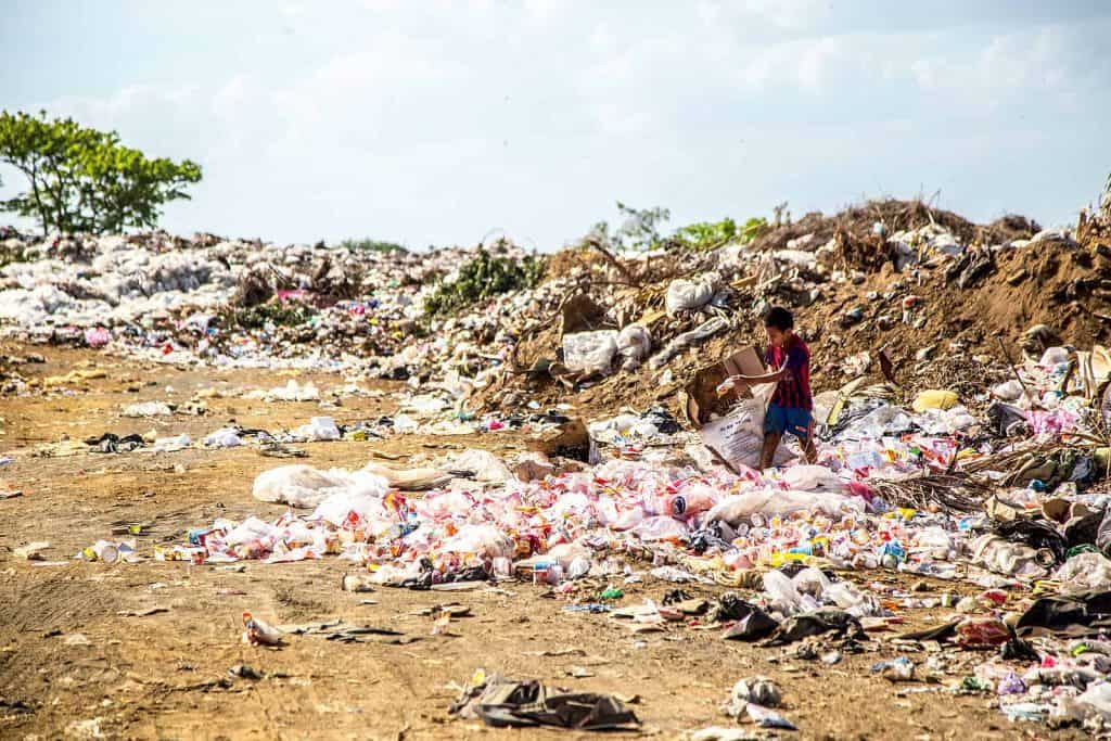 Why do we litter? Child hunting through the expanse of litter strewn across an earthly landscape.